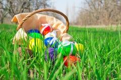 Påskägg och korg med servetten på gräs fotografering för bildbyråer