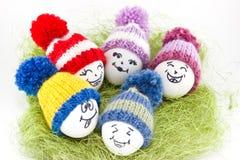 Påskägg på grön sisalhampa Emoticons i stucken hatt med pom-po Royaltyfri Foto