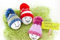 Påskägg på grön sisalhampa Emoticons i stucken hatt med pom-po Royaltyfria Bilder