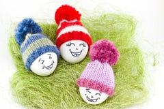 Påskägg på grön sisalhampa Emoticons i stucken hatt med pom-po Royaltyfria Foton