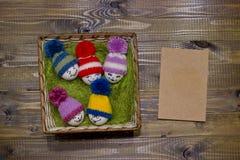 Påskägg på grön sisalhampa Emoticons i stucken hatt med pom-po Royaltyfri Bild