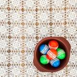 Påskägg som dekoreras med, snör åt i en bunke på den vita virkningbordduken Royaltyfri Foto