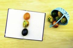 Påskägg som ligger i en blå korg och på en gul trätabell, en bok för anmärkningar som en kopia av degar och ägg som ligger på den royaltyfria foton