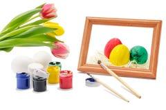 Påskägg som målas med färgpulver och borsten Arkivfoton