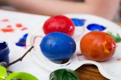 Påskägg som målas med ljus målarfärg arkivfoto