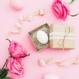 Påskägget i hantverkask och rosor blommar på rosa bakgrund Bästa sikt, lekmanna- lägenhet Påskferiebegrepp Royaltyfri Fotografi