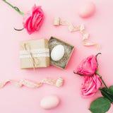Påskägget i hantverkask och rosor blommar på rosa bakgrund Bästa sikt, lekmanna- lägenhet semestrar härliga easter för bakgrund ä Royaltyfri Foto