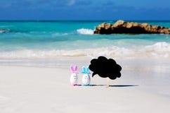 Påsk, estereggs på stranden, sand, hav och hav Arkivfoto