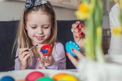 Påsk, familj, ferie och barnbegrepp - som är nära upp av liten flicka- och moderfärgläggningägg för påsk Arkivbild