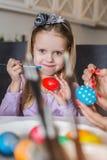 Påsk, familj, ferie och barnbegrepp - som är nära upp av liten flicka- och moderfärgläggningägg för påsk Arkivbilder