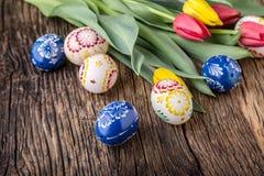 Påsk Hand - gjorda easter ägg och vårtulpan på den gamla trätabellen Arkivbild