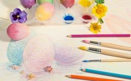 Påsk hand-målade ägg med kulöra blyertspennor, vattenfärger och vårblommor som är ordnade på kulör teckning Arkivbild