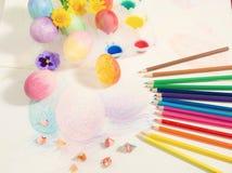 Påsk hand-målade ägg med kulöra blyertspennor, vattenfärger och vårblommor som är ordnade på kulör teckning Fotografering för Bildbyråer