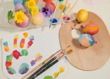 Påsk hand-målade ägg med målareborstar, träpalett, vattenfärger och vårblommor som är ordnade på kulöra fingeravtryck Royaltyfria Bilder
