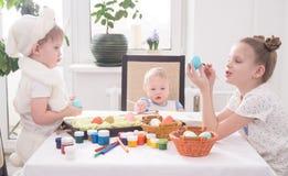 Påsk i familjcirkeln: Barn på äggen för tabellmålarfärgpåsk royaltyfri bild