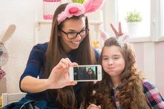 Påsk - moder och dotter med kaninöron som göras Selfie foto royaltyfri foto