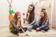 Påsk - modern och två döttrar äter chokladägg Arkivfoto