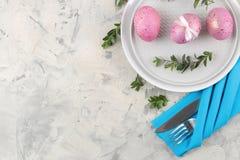 Påsk Rosa påskägg och en kniv med en gaffel och en platta på en ljus konkret bakgrund Påsktabellinställning lyckliga easter H fotografering för bildbyråer
