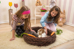 Påsk - små flickor som slår kaninerna, redet fotografering för bildbyråer