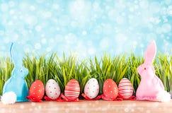 Påskbakgrund med ägg, kaniner och grönt gräs fotografering för bildbyråer