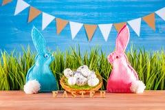 Påskbakgrund med ägg, kaniner och grönt gräs royaltyfria foton
