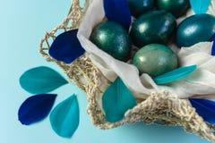 Påskbakgrund med ägg som dekoreras i blått, turkos och guld i rede med färgrika fjädrar Närbild royaltyfri fotografi