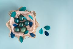 Påskbakgrund med ägg som dekoreras i blått, turkos och guld i rede med färgrika fjädrar Top beskådar kopiera avstånd royaltyfria foton