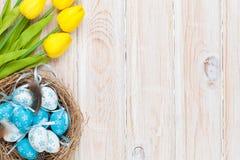 Påskbakgrund med blåa och vita ägg i redet och guling tu Arkivbilder