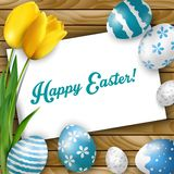 Påskbakgrund med kulöra ägg, gula tulpan och hälsningkortet över vitt trä stock illustrationer