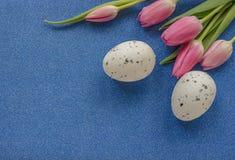 Påskbakgrund med rosa tulpan och ägget på gräsplan blänker bakgrund med kopieringsutrymme royaltyfria bilder