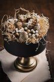Påskbakgrund med vaktelägg, fjädrar och vårris och blommor i tappningkakaställning på den lantliga tabellen för mörkt trä arkivfoto