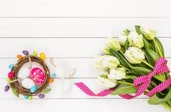 Påskbakgrund med vita blommor och dekorativa påskägg Royaltyfri Bild