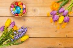 Påskbakgrund, vårblommor och färgrika påskägg på wo royaltyfria bilder