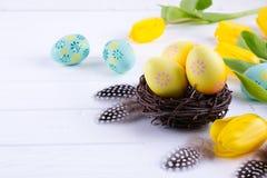 Påskbegrepp - dekorativt pilrede med dekorativa ägg, fjäder på vit bakgrund Copyspace för text arkivfoto