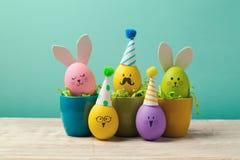 Påskbegrepp med gulliga handgjorda ägg i kaffekoppar, kanin, fågelungar och partihattar Royaltyfria Foton