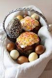 Påskbegreppssammansättning med den beautifully dekorerade påskkakan, färgade ägg, chokladägg i en korg på linnetyg arkivfoto