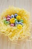 Påskchokladägg bygga bo med gula hönor. Arkivbilder