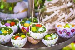 Påskdekor, hängande korgar med ägg i gräset, äggskalstunna korgar, påskgarnering Arkivbild