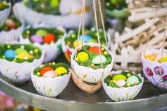 Påskdekor, hängande korgar med färgägg i gräset, äggskalstunna korgar, påskgarnering Fotografering för Bildbyråer
