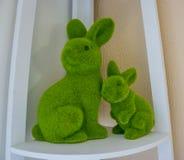 Påsken en stor grön välfylld kanin med stoppat behandla som ett barn kaningarnering på en hylla arkivbilder