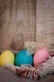 Påsken färgade ägg med pilbågen mot naturlig trätexturerad bakgrund Arkivfoto