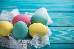 Påsken färgade ägg med snör åt bandet på blå träbakgrund Arkivbild