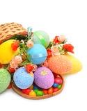 Påsken färgade plast- ägg, blommor och caramels i korgen Arkivfoto
