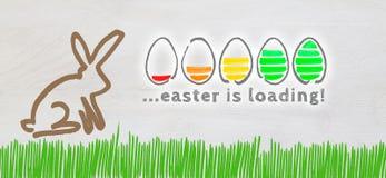Påsken laddar med färgrika ägg och påskkaninen på ljus w arkivbilder