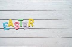 Påsken vek färgrik bokstäver för pappers- origami på lantlig bakgrund för vita träplankor Arkivfoton