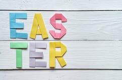 Påsken vek färgrik bokstäver för pappers- origami på lantlig bakgrund för vita träplankor Royaltyfri Foto