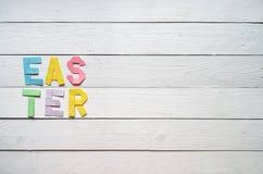 Påsken vek färgrik bokstäver för pappers- origami på lantlig bakgrund för vita träplankor Fotografering för Bildbyråer