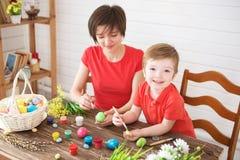 Påskförberedelser Lycklig ung moder som spenderar tid med hennes glade son Lyckliga easter för familjmamma- och barnsonmålarfärg  arkivbilder