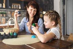 Påskferie: moder- och dottermålarfärgägg i köket och att sätta dem i en korg arkivfoto
