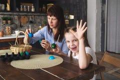 Påskferie: moder- och dottermålarfärgägg i köket och att sätta dem i en korg royaltyfria foton